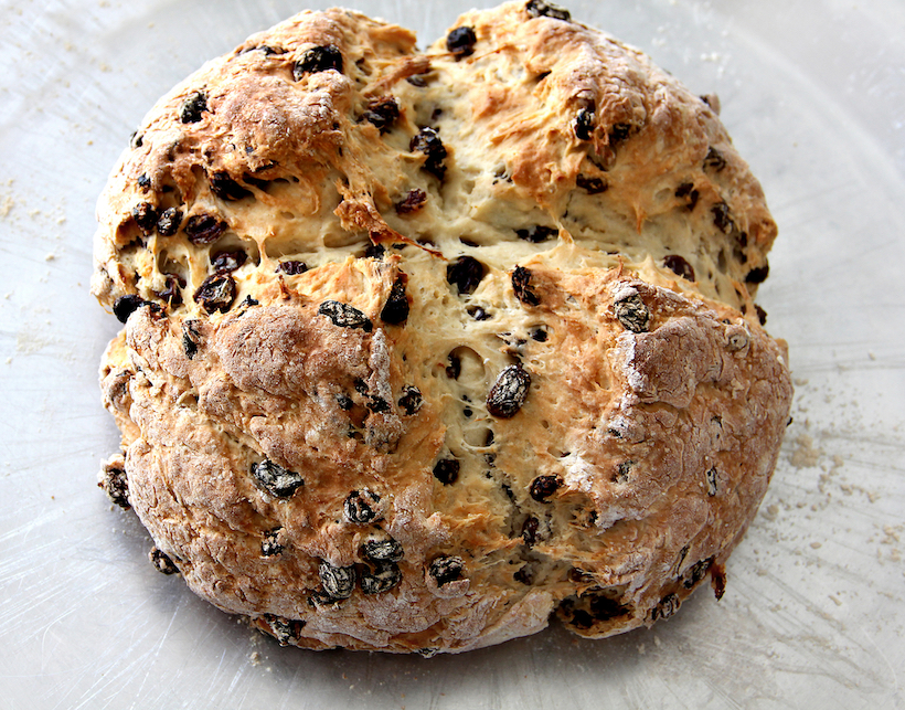 A loaf of Irish Soda Bread with raisins on baking sheet.