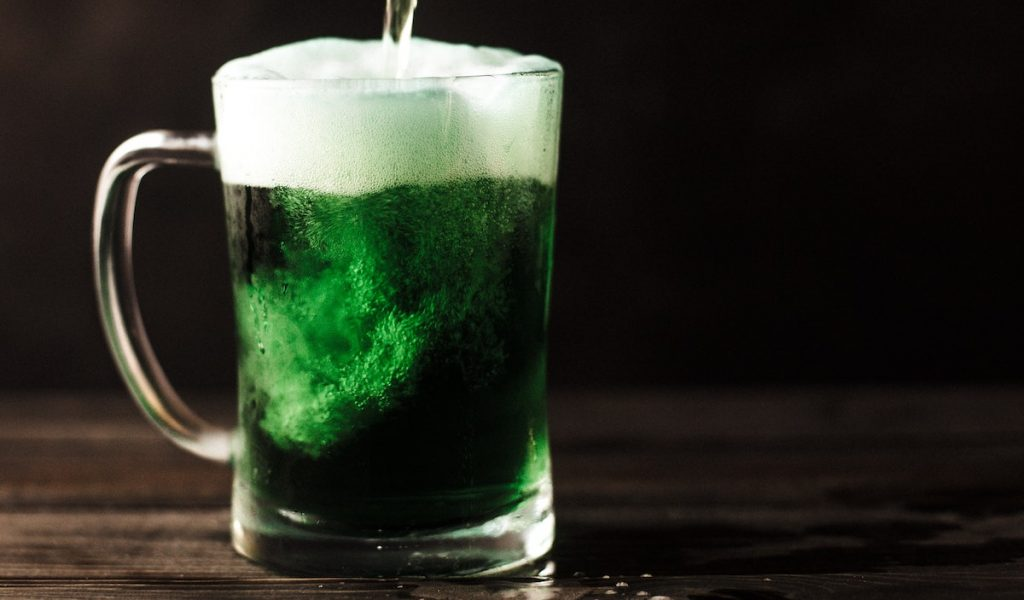 Green beer in a mug with beer being poured inside