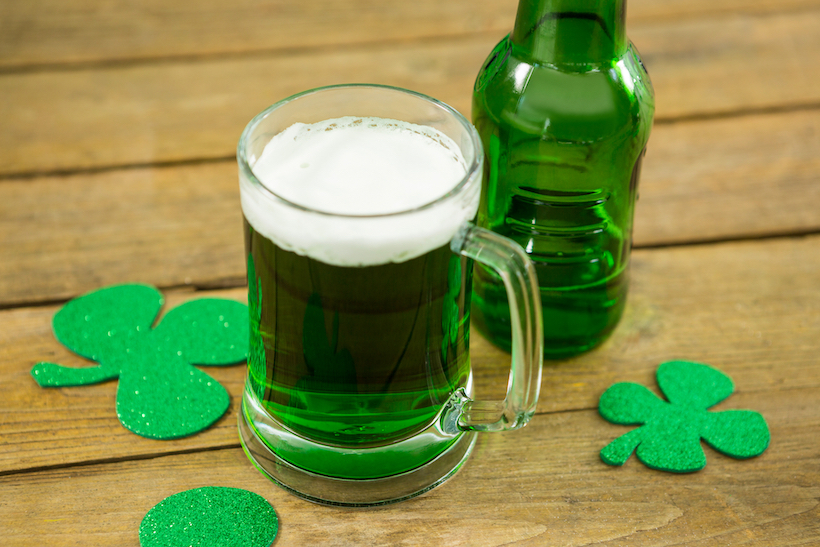 St Patricks Day green beer with shamrock on wooden surface
