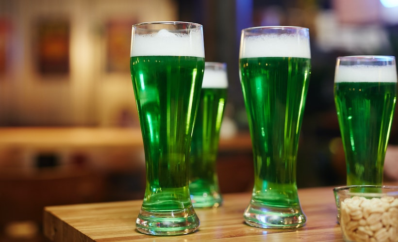 Green beers on a table with peanuts in a glass